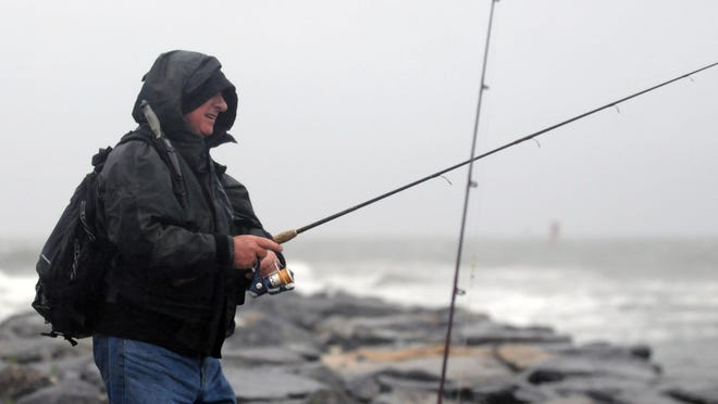 Ian Burke fishes from the rocks at the Indian River Inlet on a wet June day.