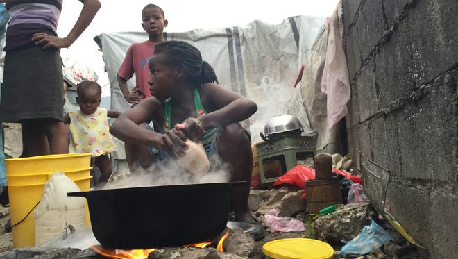 Marjorie Paul, 19, cooks rice in a tent city she has lived in for nearly 5 years. About 100 people still live in this makeshift collection of tents on the outskirts of Port-au-Prince.