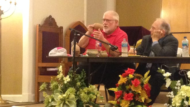Dr. Charles Page, an archaeologist, holds up an ancient artifact while Dr. Gene Davenport looks on during an interfaith discussion Thursday at Congregation B'nai Israel.