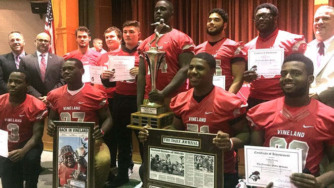 Members of the Vineland High School football team are commended for athletic and academic achievements.