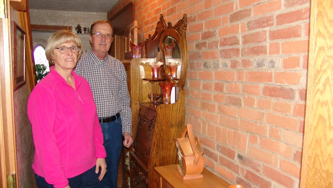 Linda and Jim Vernon stand beside a wall in the farmhouse constructed of the original brick that was made in the front yard of the property.