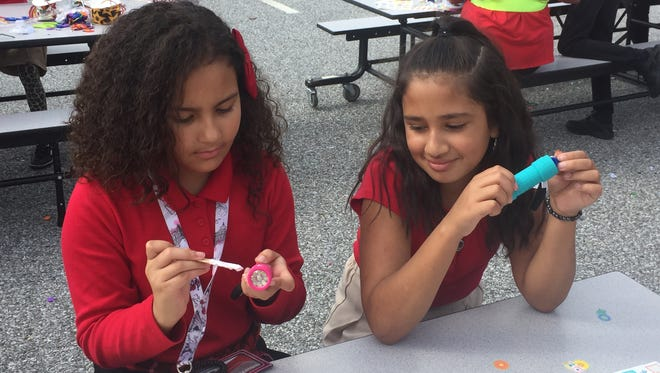 Leuchter Elementary School students Jesyana Toro (left) and Anaya Rosado decorate mini flashlights on Tuesday that will be sent to children in Puerto Rico dealing with the aftermath of Hurricane Maria.