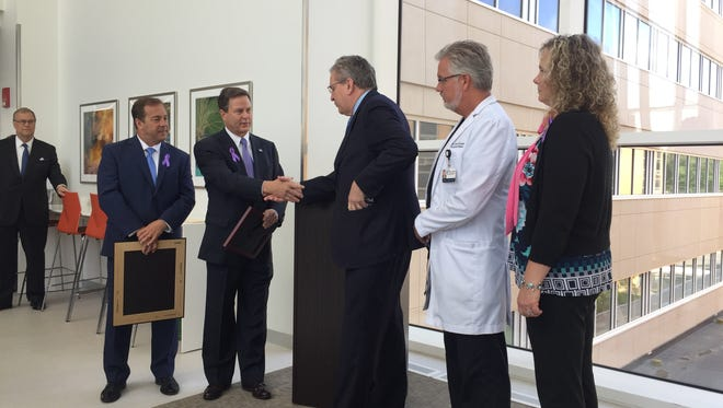 U.S. Rep. Donald Norcross shakes hands with Jefferson Health New Jersey President Joe Devine after presenting the health system with a proclamation for its work to combat heroin addiction.