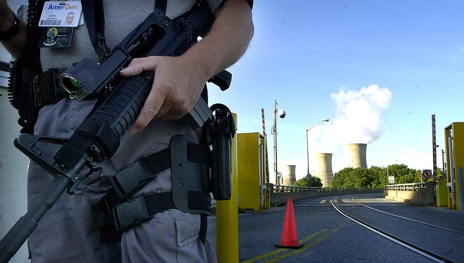Jim Buckner, a site protection officer at Three Mile Island, patrols the North Gate entrance to the nuclear power plant in 2004.