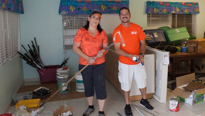 Home Depot volunteers Patricia Pilazzo and Jeff Johnston work at the Samaritan Center for Young Boys & Families, helping transform a cottage.