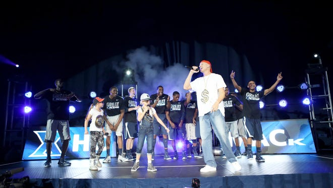 """Chris Mack and his girls, Lainee and Hailee, rap the Beastie Boys' """"Paul Revere"""" at Musketeer Madness."""