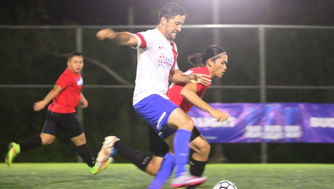 Quality Distributors' Scott Leon Guerrero stays in control of the ball against Doosan FC in a Round 2 match of the 2016 Budweiser Futsal League at the Guam Football Association National Training Center futsal court Saturday. Quality won 6-2.