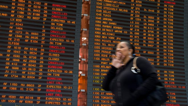 A traveler at Paris' Charles de Gaulle airport walks in front of a flight information showing some delays and cancellations because of a strike of an air traffic controllers strike.