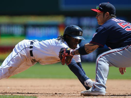 Detroit Tigers' Cameron Maybin dives back to first base ahead of the tag by the Minnesota Twins' Byung Ho Park on Wednesday, May 18, 2016 at Comerica Park in Detroit.