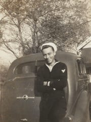 James Hudson leans against his car while on leave from the Navy during World War II