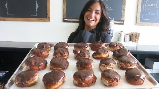 Donut Bar + Coffee shop co-owner Serena Denha displays a tray of doughnuts frosted with dark chocolate Nutella and filled with Nutella mousse.