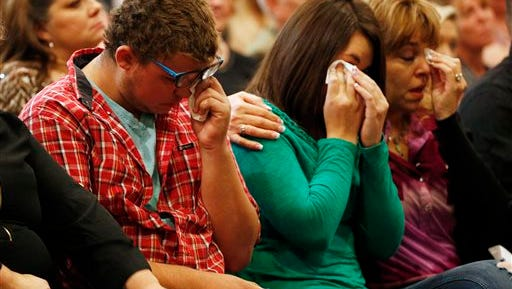From left, Mathew Downing, Lacey Scroggins and Lisa Scroggins wipe their eyes during a church service at the New Beginnings Church of God, Sunday, Oct. 4, 2015, in Roseburg, Ore. Mathew Downing and Lacey Scroggins are survivors of the shooting at Umpqua Community College. (AP Photo/John Locher)