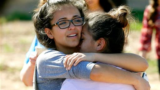 A mother and daughter reunite, Friday, Feb. 12, 2016, in Glendale, Ariz., after two students were shot and killed at Independence High School in the Phoenix suburb. The danger at the campus was over, police said, as worried parents crowded stores nearby to meet their children.