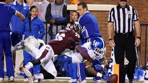 Kentucky running back Jojo Kemp (3) leaps past Mississippi State defensive back Kendrick Market (26) for a 14-yard touchdown run in the second half of their NCAA college football game at Davis Wade Stadium in Starkville, Miss., Thursday, Oct. 24, 2013. Mississippi State won 28-22. (AP Photo/Rogelio V. Solis)