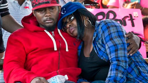 In this Oct. 19, 2014 photo Charity Guinn and Booker Hooper, mother and father of Angel Hooper, listen to speeches at a vigil for their 6-year-old daughter who was killed during a fatal shooting on Friday in Kansas City, Mo. Angel and her father had stopped to buy bubblegum at a convenience story after a jog when someone in a passing car opened fire. Authorities are vowing to find those responsible. (AP Photo/The Kansas City Star, Brian Davidson)