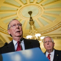Senate Majority Leader Mitch McConnell of Ky., speaks on Capitol Hill as Sen. Mike Enzi, R-Wyo., looks on.