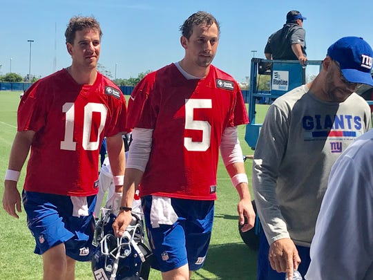 New York Giants quarterbacks Eli Manning (10) and Davis Webb (5) walk off the practice field Monday morning following the team's first OTA (offseason team activity) in East Rutherford, NJ.