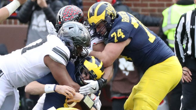 Michigan's John O'Korn is sacked by Ohio State's Michael Hill and Dre'Mont Jones as Ben Bredeson blocks in the first quarter Saturday, Nov. 25, 2017 at Michigan Stadium.