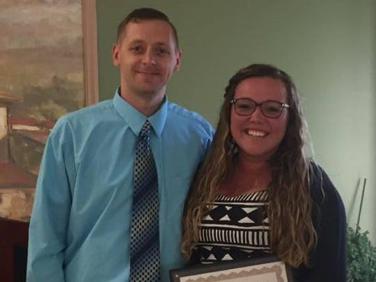 Youth Bureau Program Coordinator Adam Lawton congratulates Hannah Pastrick for her award citing her former role as a counselor with the Runaway and Homeless Program of Catholic Charities of Chemung and Schuyler Counties.