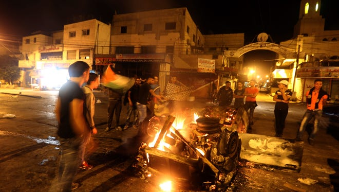 Palestinian youths stand next to a burning car belonging to an Israeli settler that was set on fire by Palestinians as it entered the northern Palestinian West Bank city of Nablus, early on Oct. 18, 2015, to visit and pray at Joseph's Tomb.
