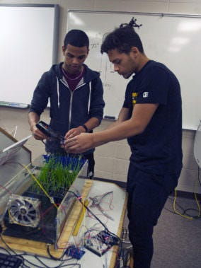 Sturgeon Bay students Andre Williams, left, and Quincy Gibson work on the mini-greenhouse they designed.