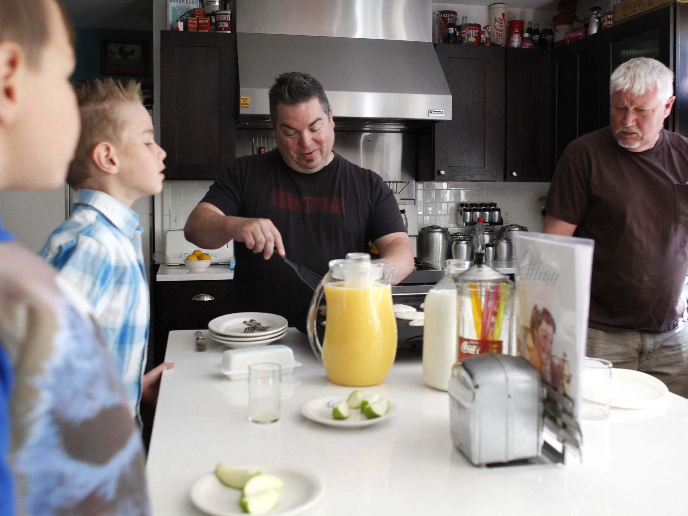 In this 2012 photo Jerry Douglass, left, and Steve Janowski cook breakfast for their two younger sons Nikolas, 4, and Joshua, 7, before leaving for Joshua's baseball game Saturday.