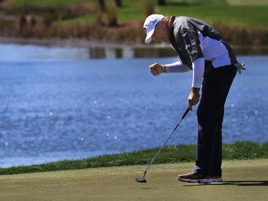 Ken Duke, of Stuart, celebrates sinking his putt on the 18th green Friday during the second round of the Honda Classic at PGA National Resort and Spa in Palm Beach Gardens. (ERIC HASERT/TREASURE COAST NEWSPAPERS)