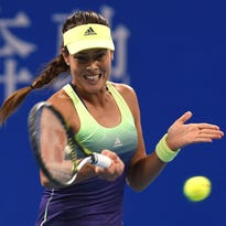 Ana Ivanovic of Serbia hits a return against Casey Dellacqua of Australia during their first round women's singles match at the China Open.