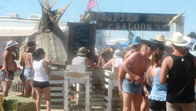 Patrons line up at the Trading Post Saloon inside the regular camping area at Night in the Country music festival, where organizers accept items in trade for drinks or dessert. This site was named the best camp site for the second year.