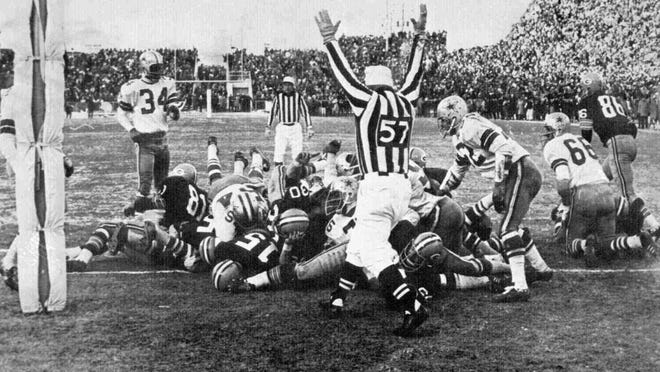 Green Bay quarterback Bart Starr (15) dives across the Lambeau Field goal line to score the winning touchdown with 13 seconds left against the Dallas Cowboys to bring the Packers their third consecutive NFL championship. The Packers defeated the Cowboys 21-17 on Dec. 31, 1967.