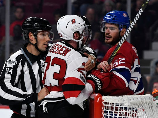 Linesman Bryan Pancich (94) steps in between New Jersey Devils forward Stefan Noesen (23) and Montreal Canadiens defenseman Eric Gelinas (52) during the first period at the Bell Centre on Thursday, Sept. 21, 2017.
