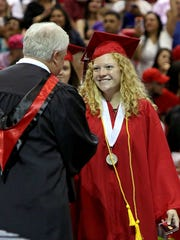 Madeleine Sons shakes hands with Wichita Falls ISD Board of Trustee Dale Harvey after being recognized as an honor graduate at the Wichita Falls High  graduation ceremony Saturday afternoon at Kay Yeager Coliseum.