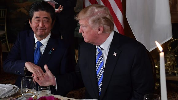 Japan's Prime Minister Shinzo Abe shakes hands with