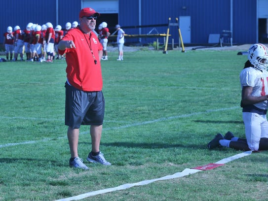 Oakland football coach Kevin Creasy instructs players