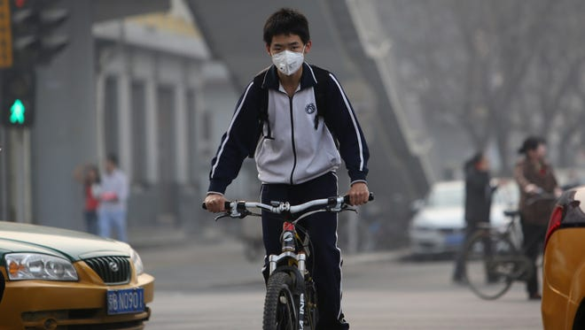 """This young boy wears a mask in Beijing as environmental authorities issued a """"yellow"""" smog alert for the capital on March 26, 2014."""