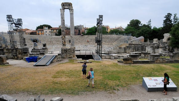 Tourists explore the amphitheater of Arles.