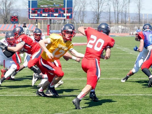 Former Chambersburg quarterback Ryan Martin (12) makes a handoff during Shippensburg University's spring game. Martin is in the mix for what is currently an open starting QB spot on the Red Raiders roster.