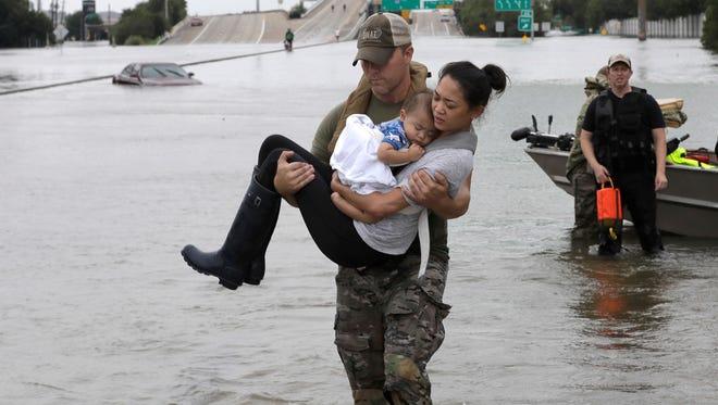 Houston SWAT officer Daryl Hudeck rescues Catherine Pham in Houston on Aug. 27, 2017.