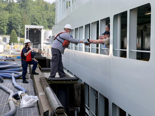 A worker at the Manchester Fuel Depot passes a fuel line coupling ito crew members on the ferry Chimacum on Monday.