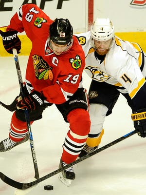 Blackhawks center Jonathan Toews (19) takes the puck from Predators defenseman Ryan Ellis (4).