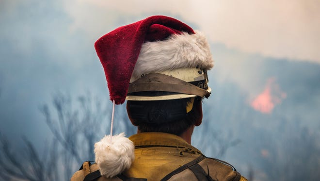 A firefighter wearing a Santa hat looks onto controlled burn operation Wednesday as the efforts slowed down on the Thomas Fire.