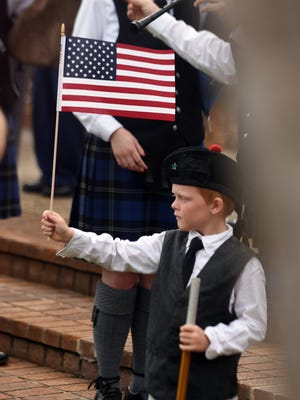 Brett Bailey, 7, with the PCS Pipe Band Pipers holds up an American flag during the 34th annual memorial day service on Monday at Veterans Memorial Park in Hattiesburg.