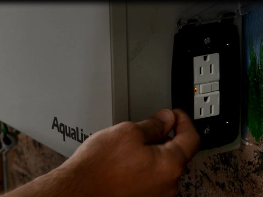 Stephen Little, a licensed pool contractor and president of Claro Pools, shows a ground-fault circuit interrupter that is inappropriate for pool lights because an appliance can be plugged into it.