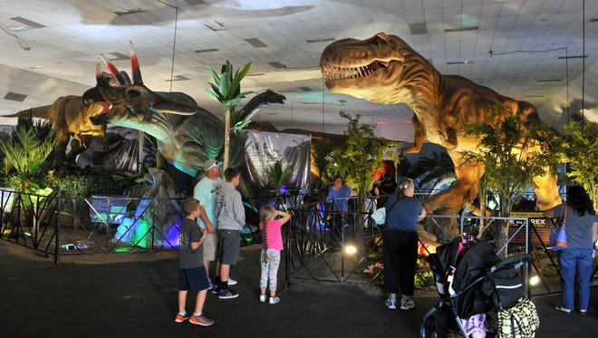 Crowds get a look at life-size animatronic dinosaurs on display last year.