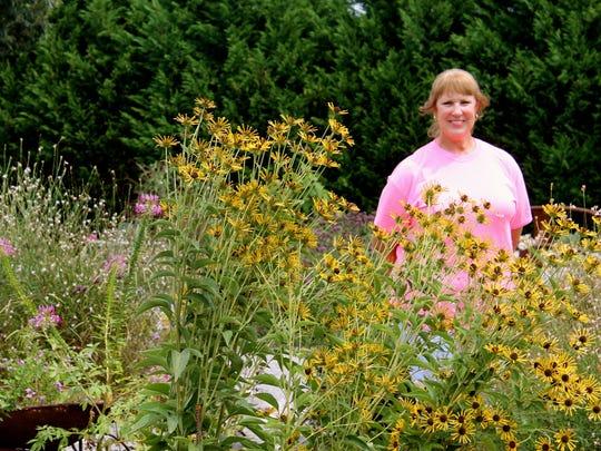 Master Gardener Christy Morrow stands in her extensive garden.