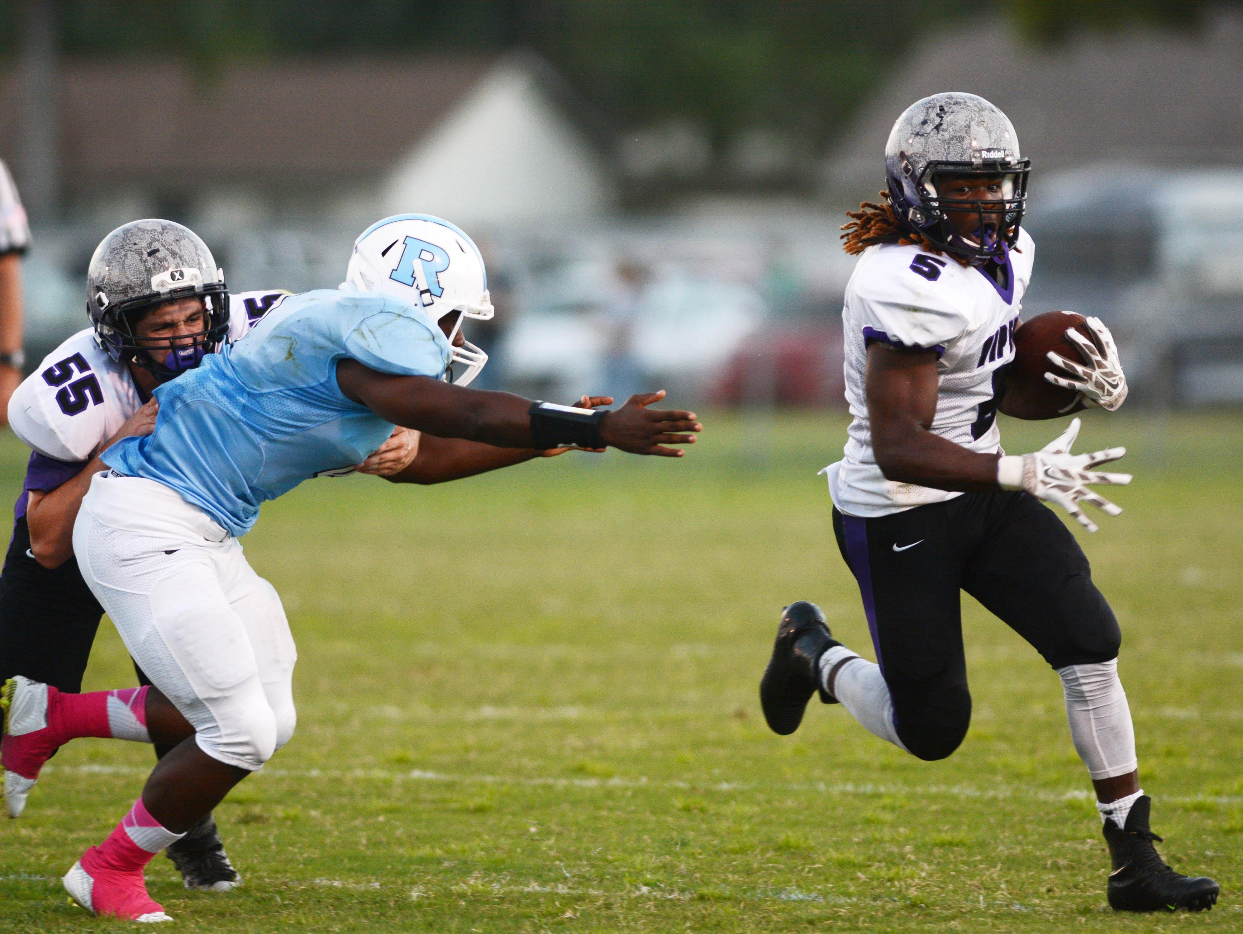 Corn Fulton of Space Coast runs away from the tackle of Rockleldge's LaQuentin Hastie during Friday's game at McLarty Stadium.