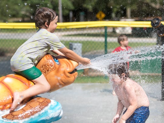 Asa Taylor, 5, right, walks face first into a stream of water during the grand opening of the new Dolphin Island Splash Pad at Sunset Kids Park in Gulf Breeze on Wednesday, May 30, 2018.