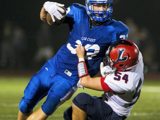 Cedar Crest's Evan Horn is brought down by Nicholas Bradley, of Lebanon, during the 2015 Cedar Bowl at Earl Boltz Stadium on September 4.