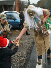 A character from the Hog Tails float hands out candy to a child Sunday at the Denver Downs Christmas Parade.
