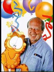 Jim Davis, right, with Garfield